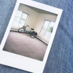Photograph of a mint green tricycle in an empty room